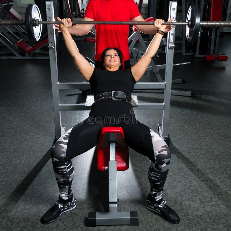 Vrouw die plus grootte in gymnastiek oefeningen met barbell doen powerlift, F royalty-vrije stock foto's