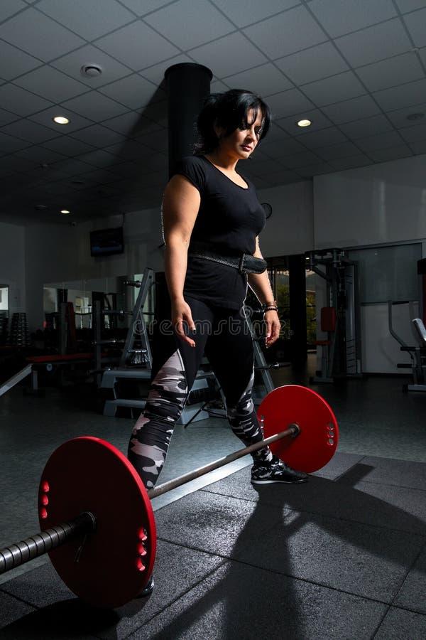 Vrouw die plus grootte in gymnastiek oefeningen met barbell doen powerlift, F royalty-vrije stock fotografie