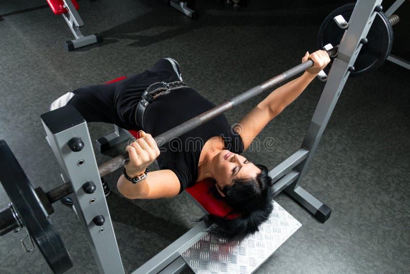 Vrouw die plus grootte in gymnastiek oefeningen met barbell doen powerlift, F royalty-vrije stock foto