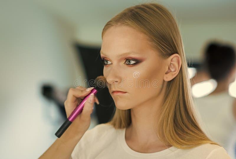 Vrouw die poeder op wang met borstel, make-up krijgen De hand van make-upkunstenaar is bloost op modelgezicht van toepassing Vrou royalty-vrije stock foto's