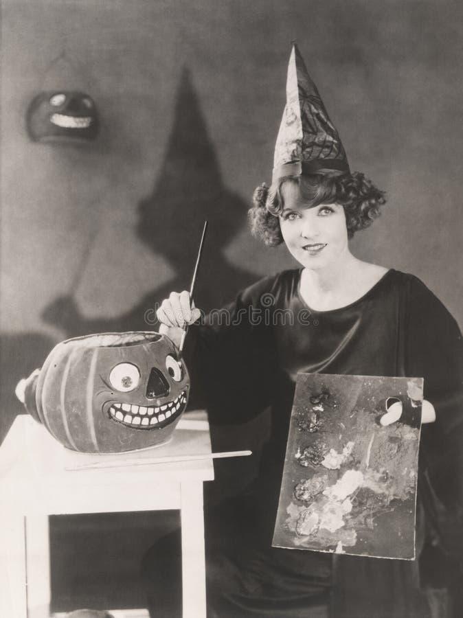 Vrouw die in pointy hoed een o'lantern hefboom schilderen royalty-vrije stock fotografie