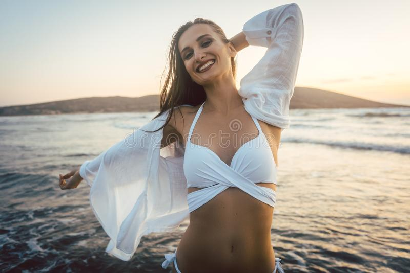 Vrouw die pret hebben bij het strand tijdens zonsondergangtijd royalty-vrije stock foto