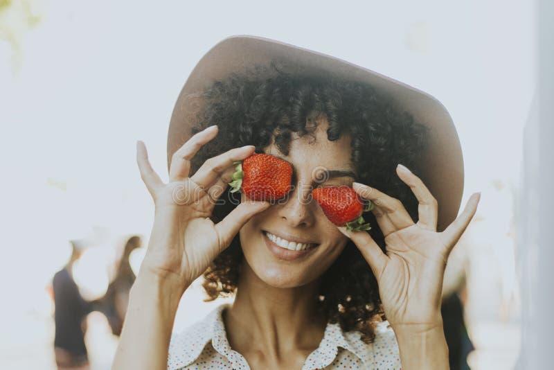 Vrouw die pret met aardbeien hebben stock foto's