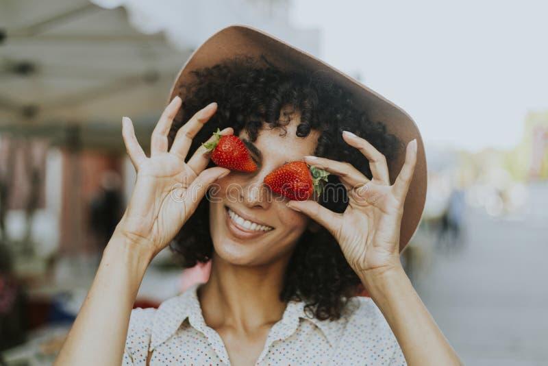Vrouw die pret met aardbeien hebben stock foto