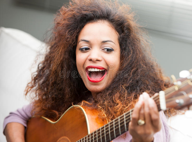 Vrouw die pret met haar gitaar hebben royalty-vrije stock fotografie