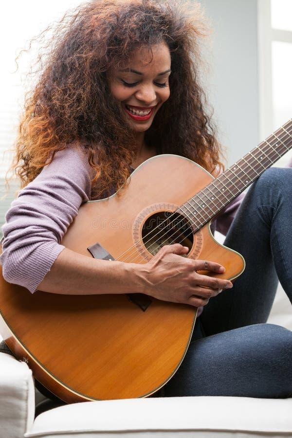 Vrouw die pret met haar gitaar hebben royalty-vrije stock afbeelding