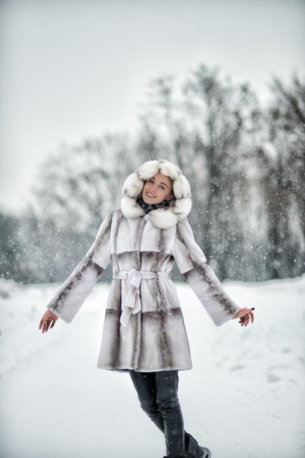 Vrouw die pret op de sneeuw in de winterbos hebben stock fotografie