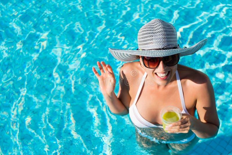 Vrouw die pret op de zomervakantie hebben in zwembad stock foto's