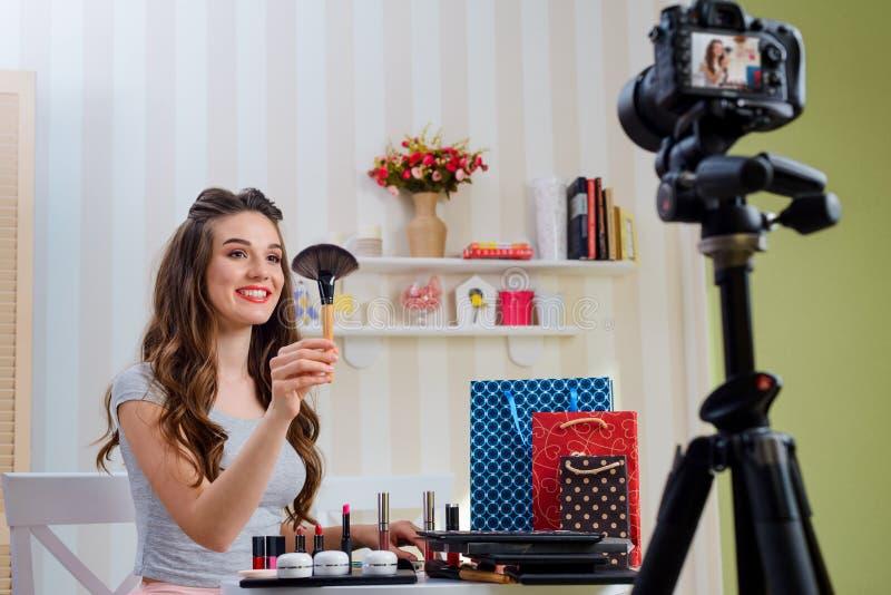 Vrouw die professionele poederborstel voorstellen stock foto's