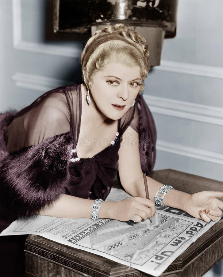 Vrouw die raadsel in krant doen (Alle afgeschilderde personen leven niet langer en geen landgoed bestaat Leveranciersgaranties di stock afbeelding