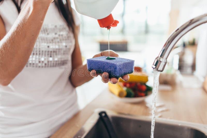 Vrouw die reinigingsmiddel zetten aan een spons De schotels van de handwas stock afbeeldingen