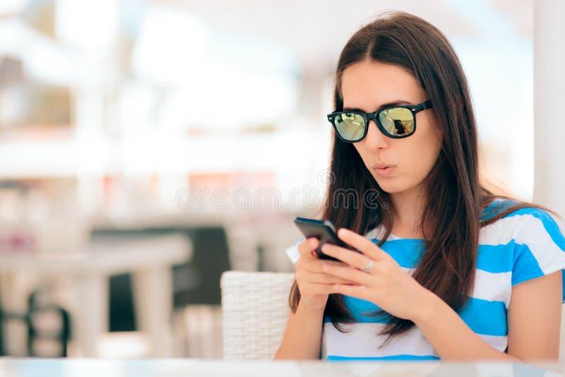 Vrouw die in Restaurant haar Smartphone-Berichten controleren royalty-vrije stock afbeelding