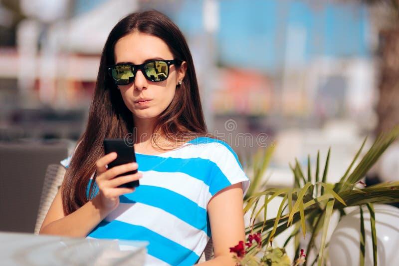 Vrouw die in Restaurant haar Smartphone-Berichten controleren stock afbeelding