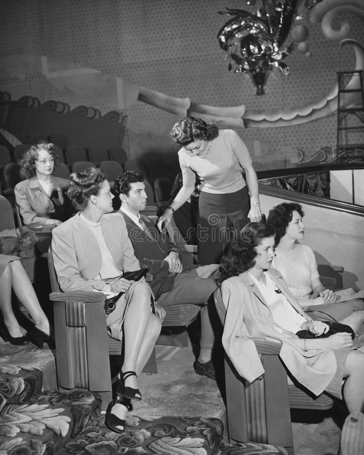 Vrouw die rij van publiek in theater verlaten (Alle afgeschilderde personen leven niet langer en geen landgoed bestaat Th van lev stock fotografie