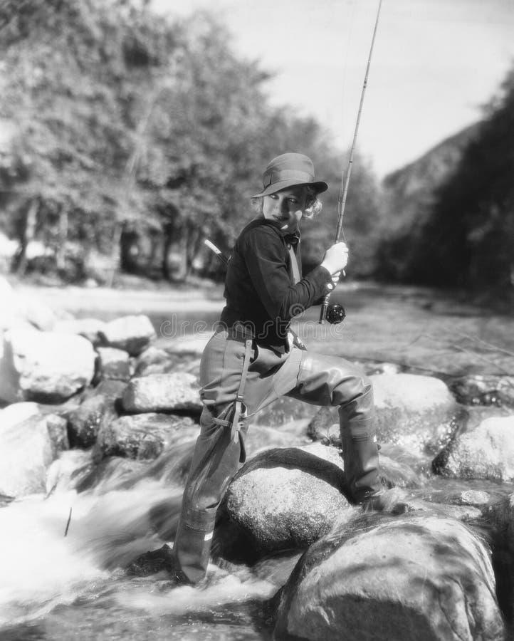 Vrouw die in rivier vissen (Alle afgeschilderde personen leven niet langer en geen landgoed bestaat Leveranciersgaranties dat er  royalty-vrije stock afbeeldingen
