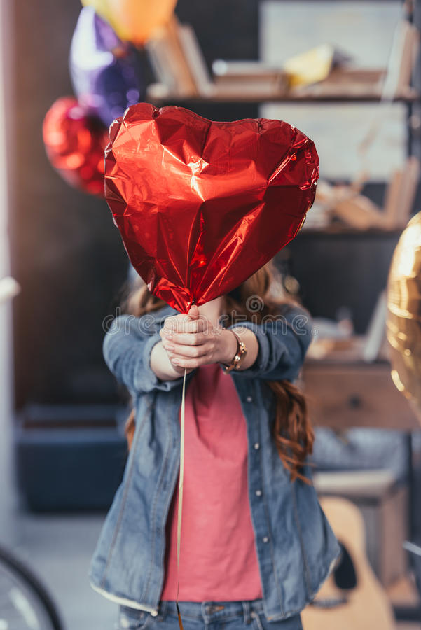 Vrouw die rode ballon houden en zich in slordige ruimte na partij bevinden stock afbeelding