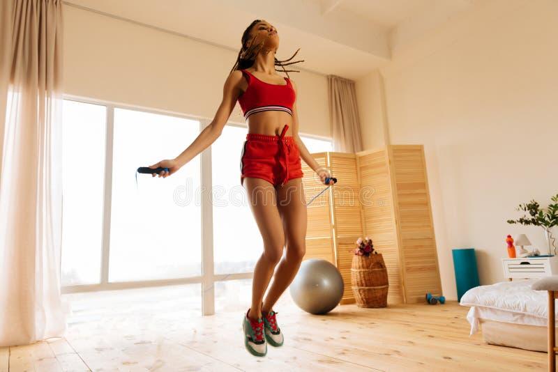 Vrouw die rode borrels en tennisschoenen dragen die de kabel thuis overslaan stock afbeelding