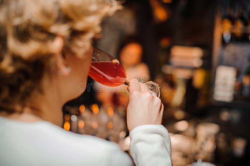 Vrouw die rode cocktail van kristalwijnglas nippen bij het restaurant royalty-vrije stock fotografie