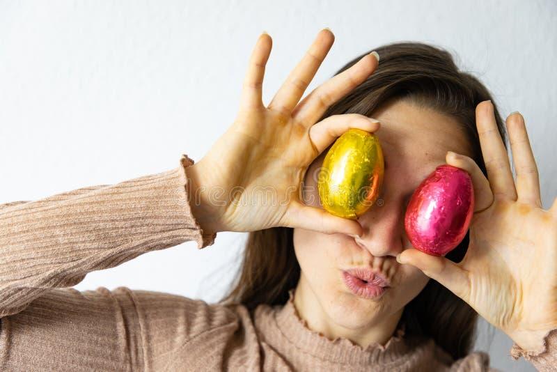 Vrouw die rode en gouden chocoladepaaseieren voor haar ogen houden royalty-vrije stock foto's