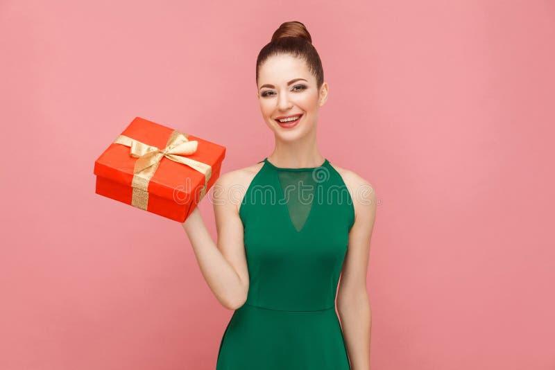 Vrouw die rode giftdoos en het toothy glimlachen houden stock foto's