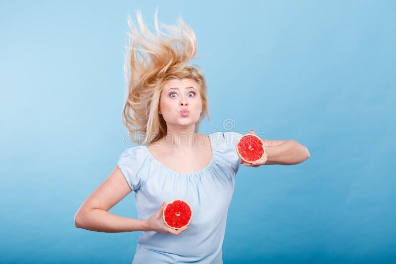 Vrouw die rode grapefruit houden die gek windblown haar hebben royalty-vrije stock afbeeldingen