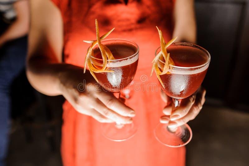 Vrouw die in rode kleding drie glazen met verse cocktails houden stock afbeeldingen
