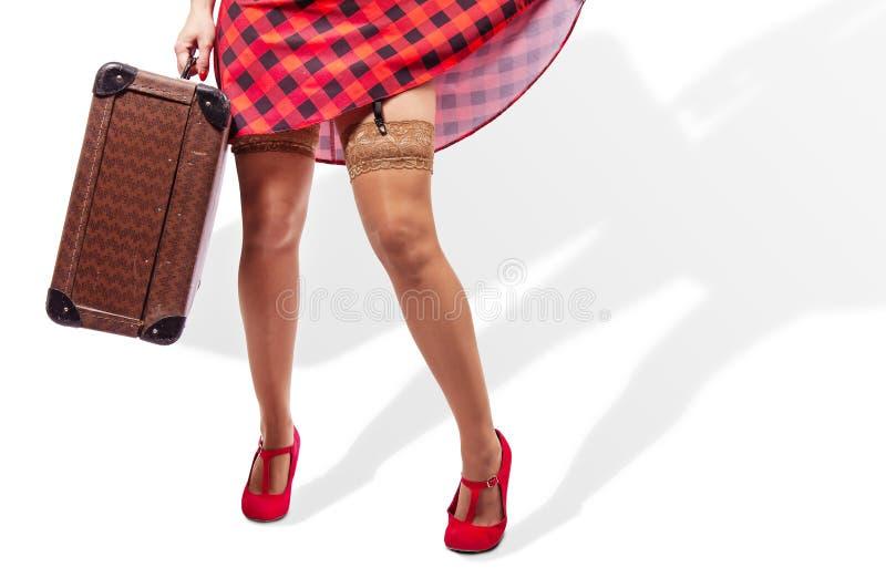 Vrouw die in rode kleding een koffer houden benenclose-up stock foto