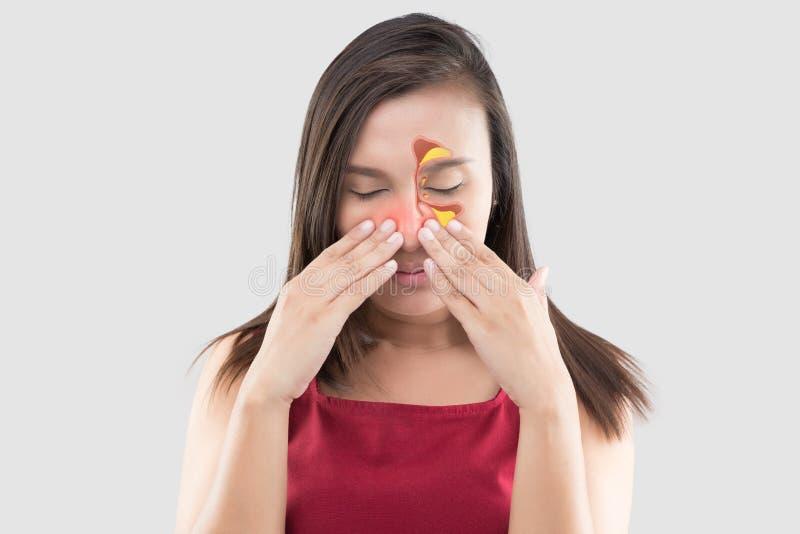 Vrouw die in rode slijtage onwel wegens sinus tegen een grijze achtergrond voelen De mensen vingen een koude en een koorts royalty-vrije stock afbeeldingen