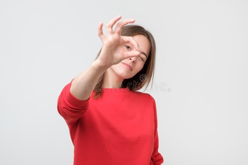 Vrouw die rode sweater dragen die o.k. gebaar doen die, oog die door vingers kijken glimlachen stock afbeelding