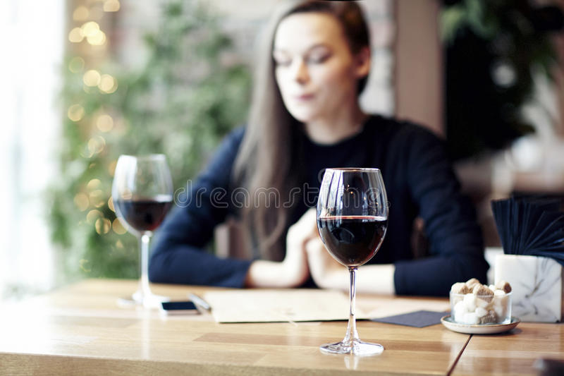 Vrouw die rode wijn in koffie drinken en rust hebben dichtbij venster royalty-vrije stock foto