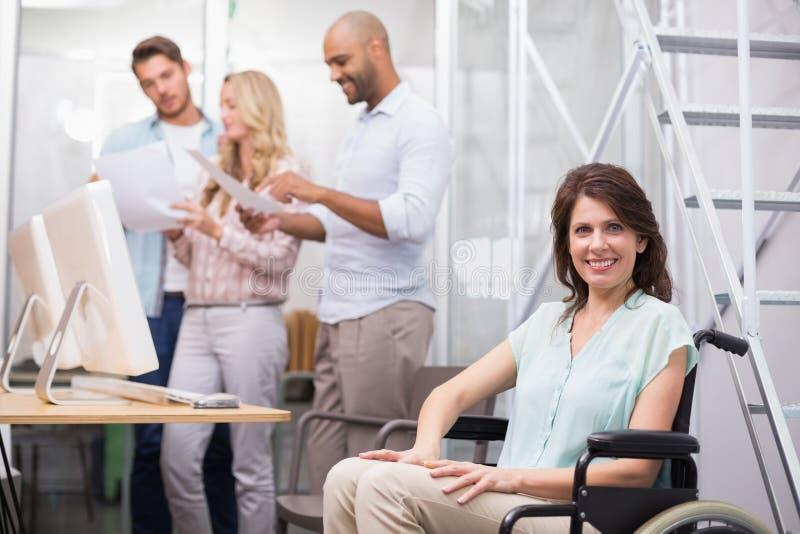 Vrouw die in rolstoel bij camera met team achter haar glimlachen royalty-vrije stock fotografie
