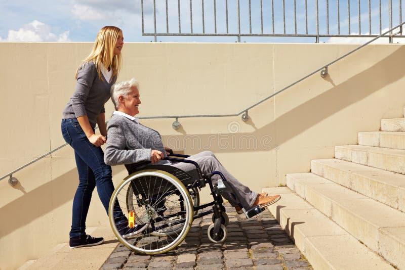 Vrouw die rolstoelgebruiker helpt stock fotografie