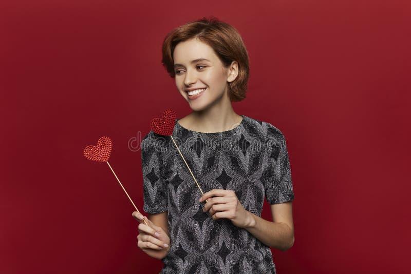 Vrouw die rood hart in handen houden, de dagconcept van de valentijnskaart, rode achtergrond, gelukkig wijfje royalty-vrije stock afbeelding