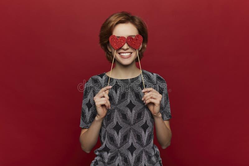 Vrouw die rood hart in handen houden, de dagconcept van de valentijnskaart, rode achtergrond, gelukkig wijfje royalty-vrije stock foto's