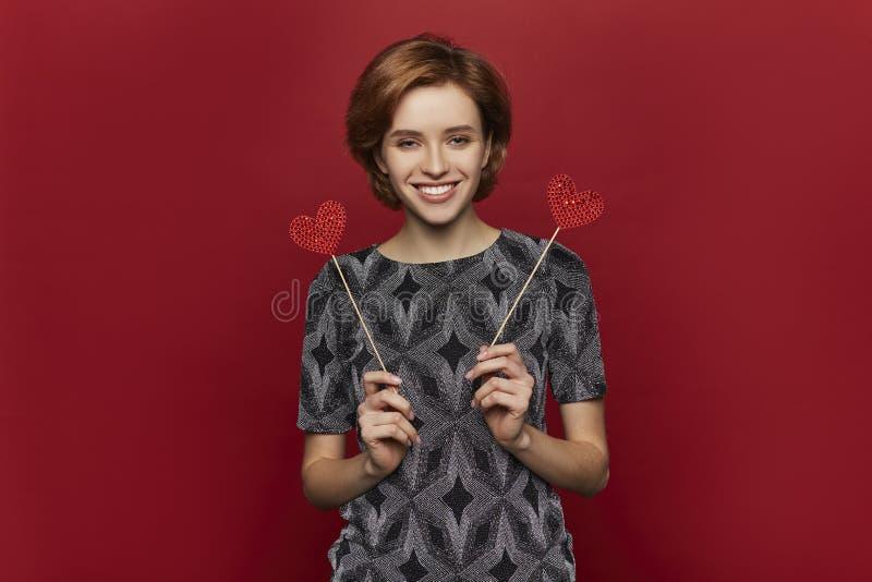 Vrouw die rood hart in handen houden, de dagconcept van de valentijnskaart, rode achtergrond, gelukkig wijfje royalty-vrije stock foto