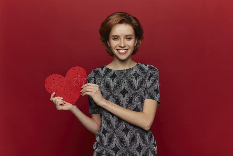 Vrouw die rood hart in handen houden, de dagconcept van de valentijnskaart, rode achtergrond, gelukkig wijfje stock afbeeldingen