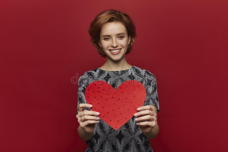 Vrouw die rood hart in handen houden, de dagconcept van de valentijnskaart, rode achtergrond, gelukkig wijfje stock foto