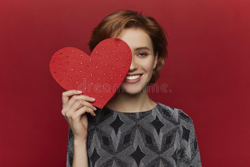 Vrouw die rood hart in handen houden, de dagconcept van de valentijnskaart, rode achtergrond, gelukkig wijfje stock foto's
