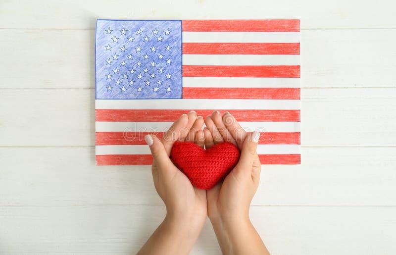 Vrouw die rood hart houden dichtbij tekening van Amerikaanse nationale vlag op witte houten lijst royalty-vrije stock afbeelding