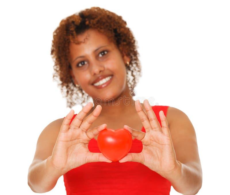 Vrouw die rood hart tonen stock foto's