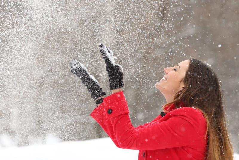 Vrouw die in rood sneeuw in de lucht in de winter werpen stock afbeeldingen