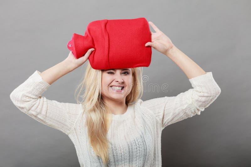 Vrouw die roodgloeiende waterfles op hoofd houden royalty-vrije stock foto's