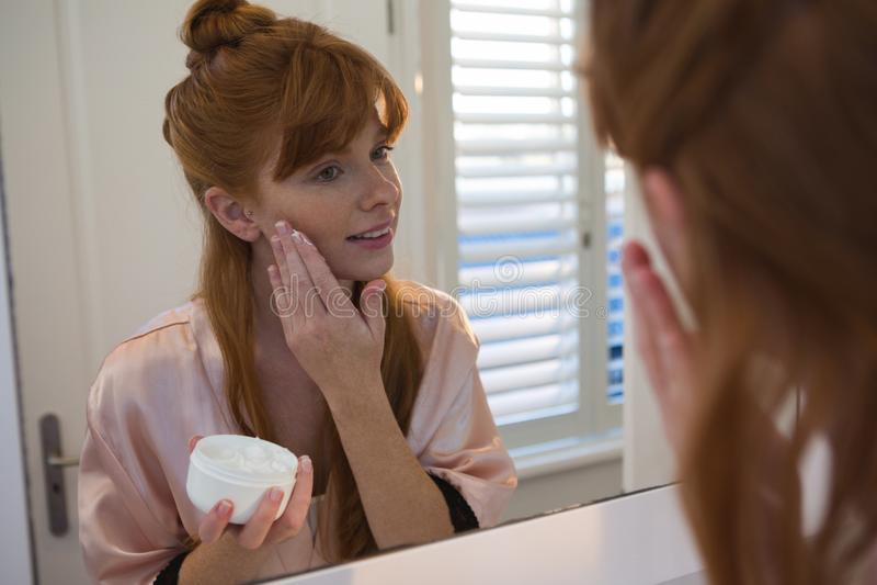 Vrouw die room op haar gezicht in badkamers toepassen royalty-vrije stock fotografie