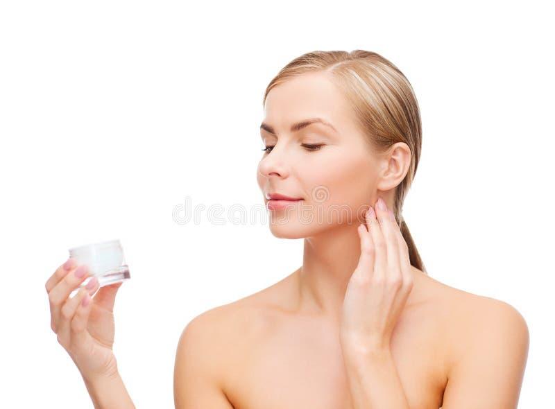 Vrouw die room op haar huid toepassen stock fotografie