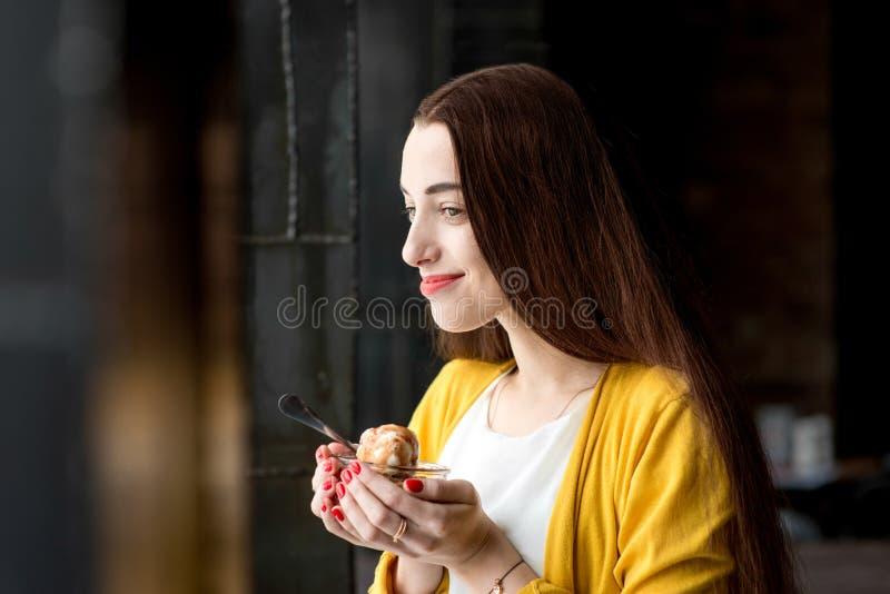Vrouw die roomijs in de koffie eten stock foto