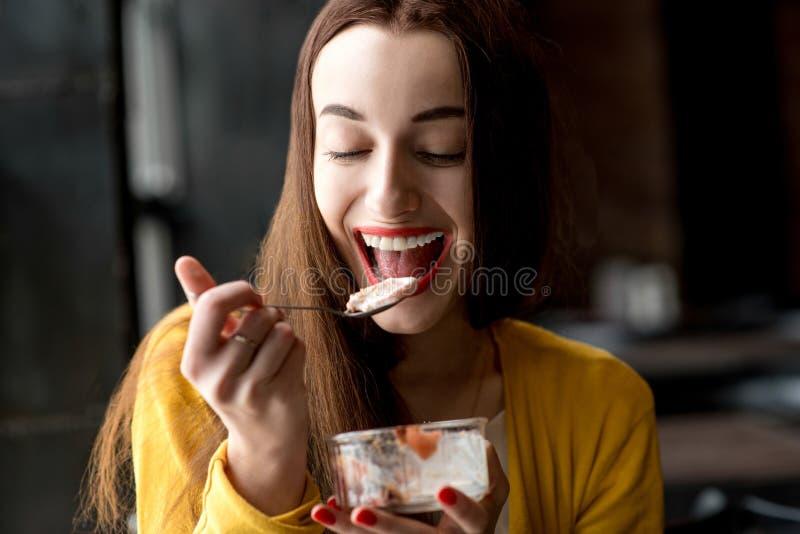 Vrouw die roomijs in de koffie eten stock fotografie