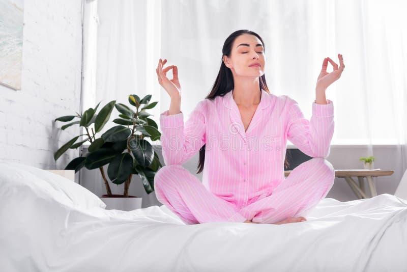vrouw die in roze pyjama's in lotusbloem de zitten stelt op bed in ochtend stock foto