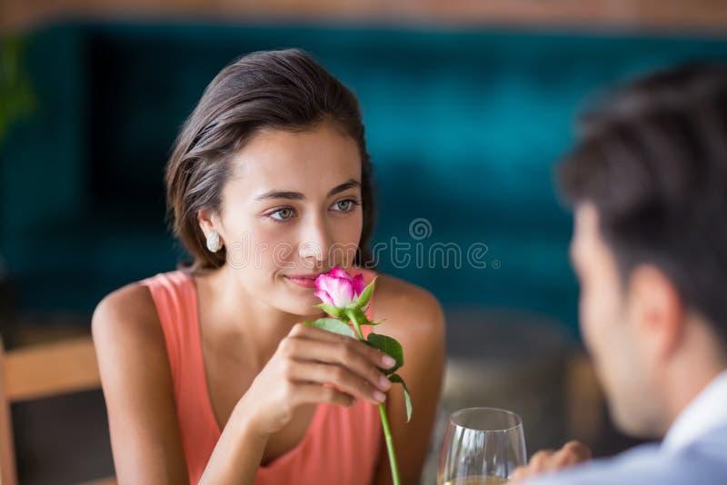 Vrouw die roze ruiken aangeboden door de mens stock afbeeldingen