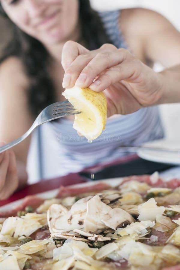 Vrouw die rundvleescarpaccio in intalian restaurant eten royalty-vrije stock afbeelding