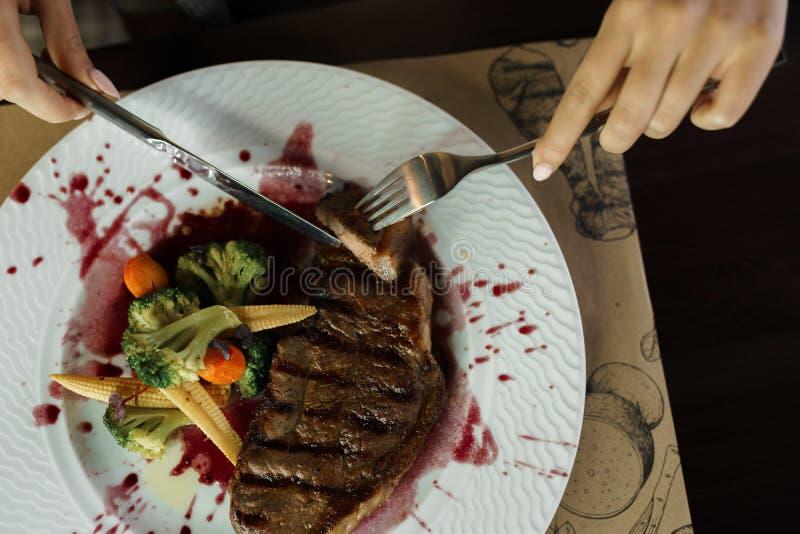 Vrouw die rundvleeslapje vlees 'Striploin 'in wijnsaus eet, op een lijst stock foto